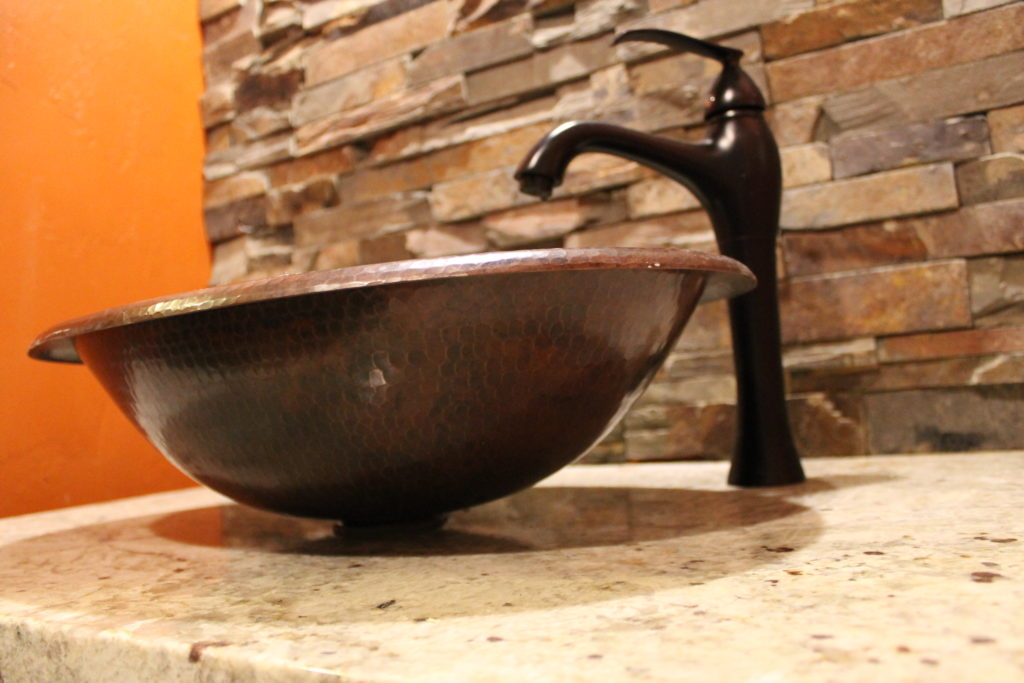 copper vessel sink in powser room with stone wall