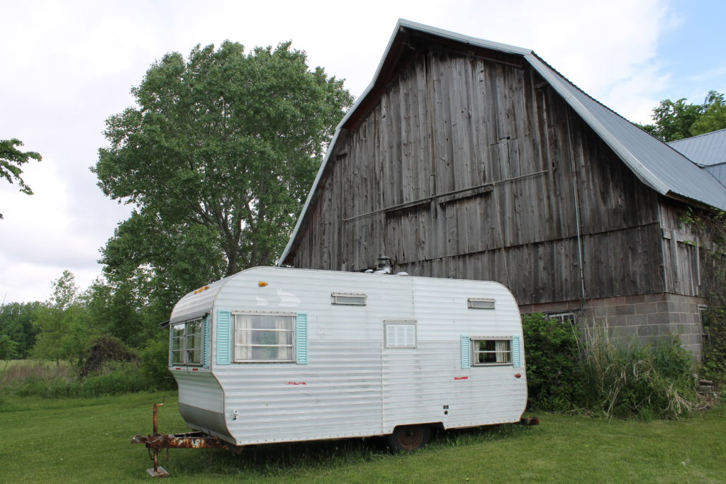 camper in front of barn