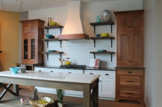farmhouse-kitchen-with-white-and-stained-cabinets-decorative-range-hood-and-open-shelving