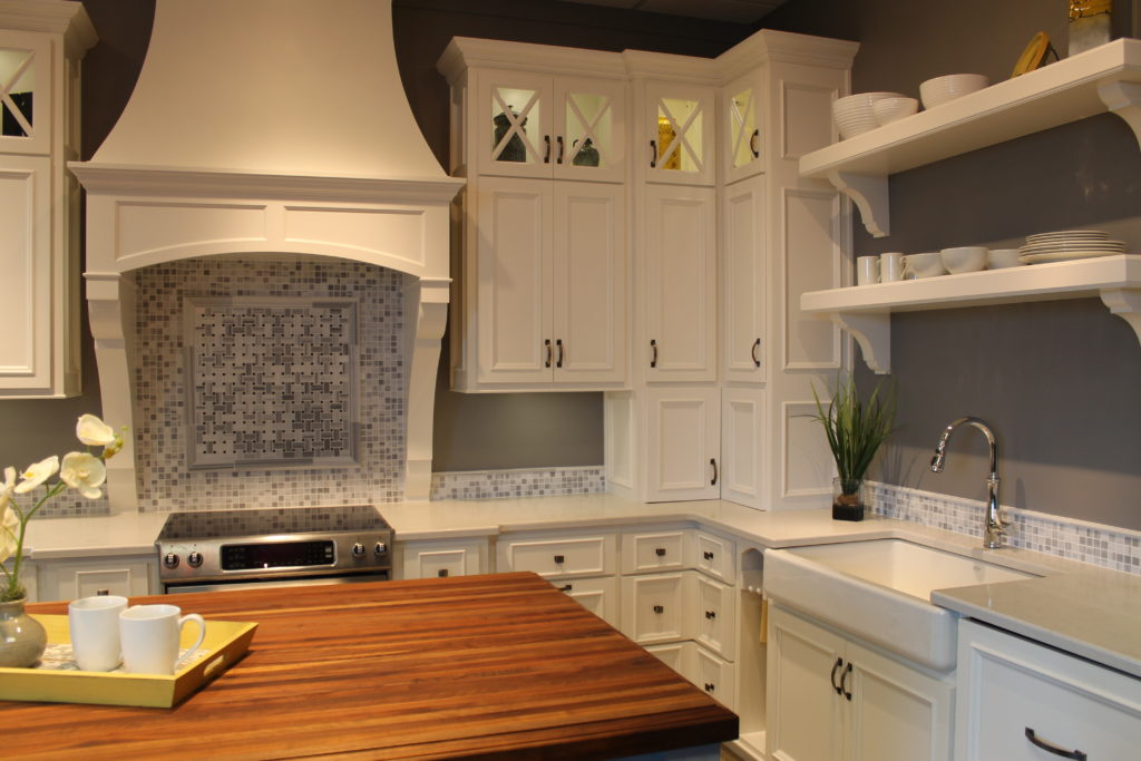 butcher block on the island gives this all white kitchen a pleasant